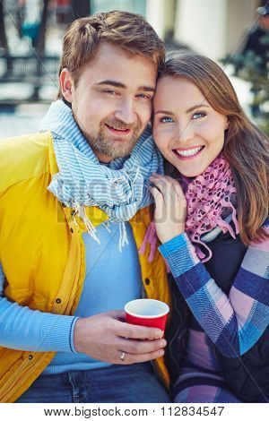 Amorous couple in casual-wear looking at camera outdoors