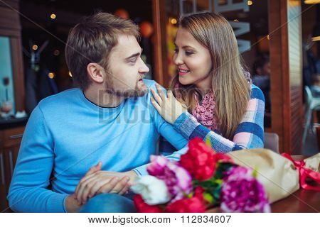 Amorous couple in casual-wear relaxing in cafe
