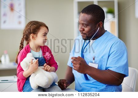Cute girl with teddybear looking at clinician at hospital