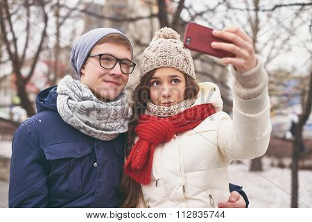 Amorous dates in winter-wear making selfie