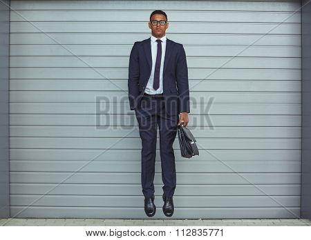Elegant businessman with briefcase jumping against jalousie