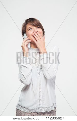Attractive smiling young woman in white blouse covered mouth with hand and talking on smartphone over white background