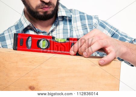 Close up of concenrated bearded young man in plaid shirt using spirit level over white background