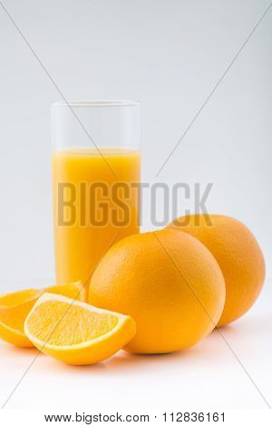 Whole oranges with cut ones and glass of juice.
