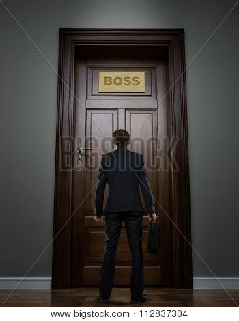 Businessman In Front Of The Huge Door