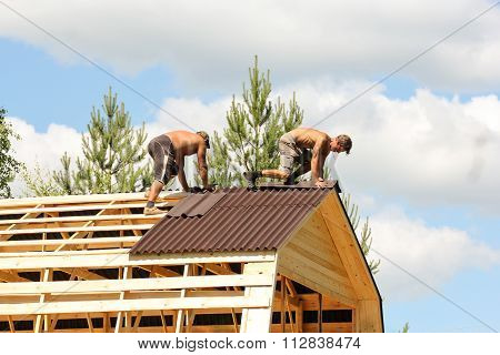 Workers Working On The Roof Ridge.