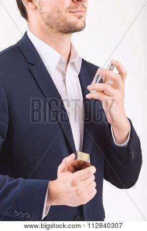 Man spraying perfume over himself.