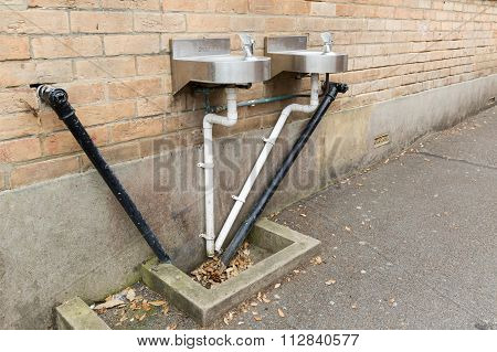 A Photo Of Black And White Angular Water Pipes Connected To  Two Stainless Steel Basins On A Beige B
