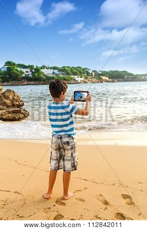 The young man  traveler photographing sea island view with digital tablet on pier of boat station.