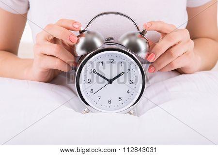 Female hands and alarm clock