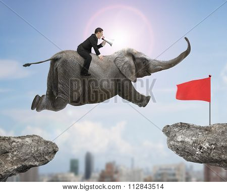 Man With Using Speaker Riding Elephant Flying Toward Red Flag