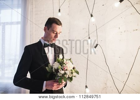 Handsome Young Groom In A Tuxedo With A Butterfly Is Holding A Winter Bridal Bouquet