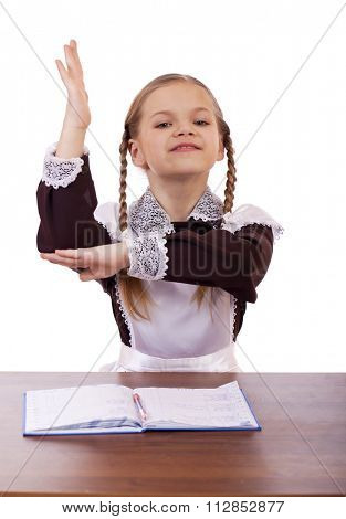 Ready to answer questions. Young beautiful schoolgirl sitting at a desk, isolated on a white background