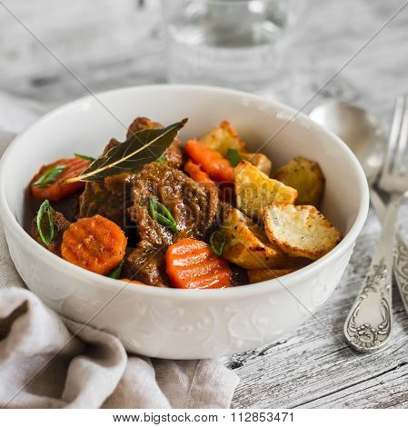 Beef Stew In Tomato Sauce And Roasted Potatoes In A White Bowl On A Light Wooden Background