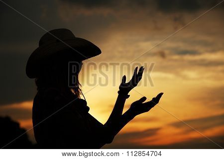 Young Girl Near Haystacks In Cowboy Hat At Sunset