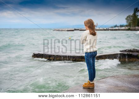 Cute little girl of 8 years old playing by the lake