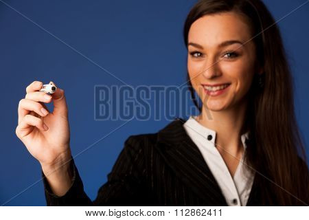 business woman with blue eyes, writes on a glass table with marker presenting business opportunities