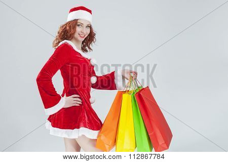 Female Santa Helper with Shopping Bags Against White