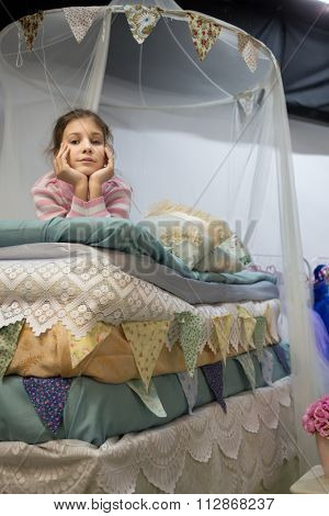 One little girl is laying on the many mattresses under a bed curtain.