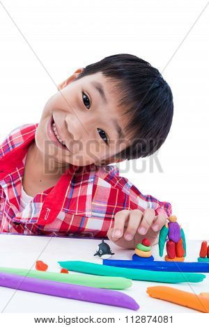 Child Show His Works From Clay, On White. Strengthen The Imagination