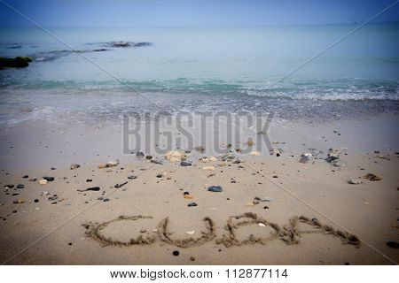 Cuba word written in the sand with tropical beach in the background