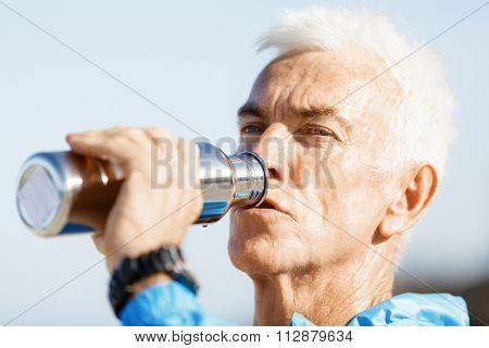 Handsome healthy man in sport wear drinking from sports bottle