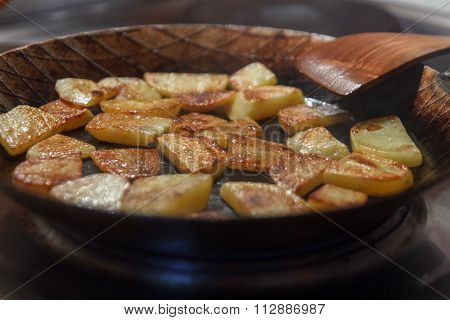 Crispy brown chip potatoes in iron frying pan with spatula