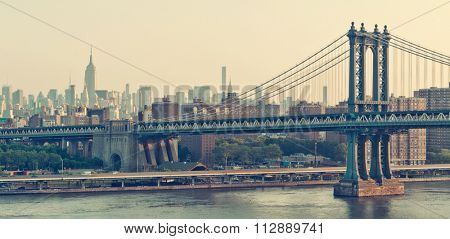New York City panorama with the historic Manhattan Bridge suspension bridge crossing the East River at sunrise with a colorful orange sky