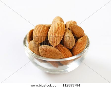 glass bowl of raw almonds on a white background