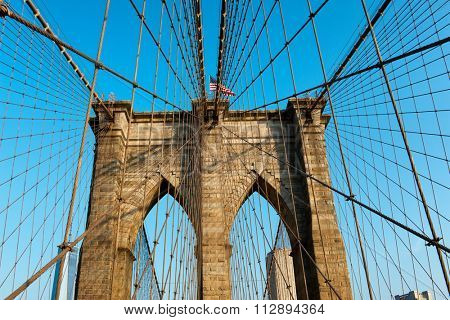 Network of suspension cables attached to one of the towers on the historic steel suspension bridge of Brooklyn Bridge, New York, against a clear blue sky