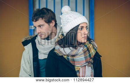 Couple wearing winter clothes standing and looking sideways