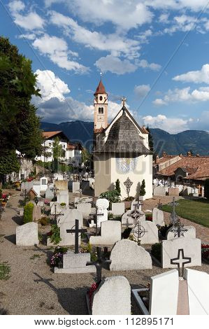 Cemetery and parish church in Dorf Tirol with mountains in the background