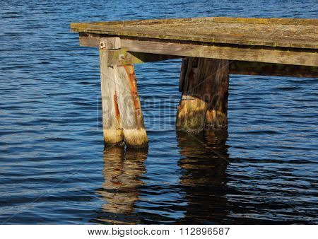 Wooden Pier End With Dark Water Reflection