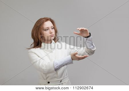 Woman holding something in hands on gray background