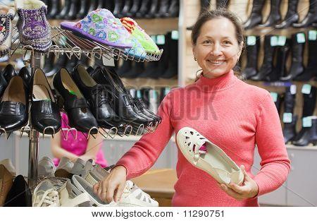 Woman Chooses Shoes At Shoes Shop