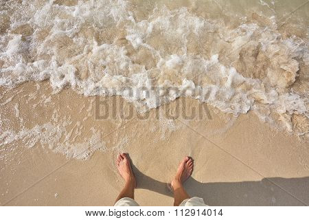 Man's legs on the sand beach and sea waves