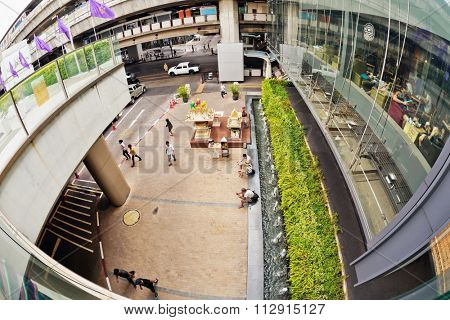 BANGKOK, THAILAND- APRIL 30, 2015: People rest near entrance to the Siam Paragon shopping mall- one of the biggest shopping center in Asia. It includes a wide range of specialty stores and restaurants
