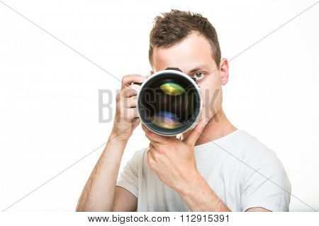 Young pro photographer with digital camera - DSLR and a huge telephoto lens in his well equiped studio, taking photos (color toned image; shallow DOF)