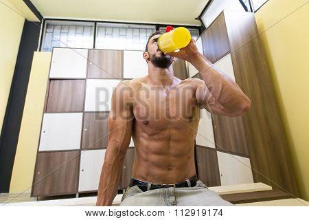 Handsome Muscular Man Drinking Protein Drink In Locker Room