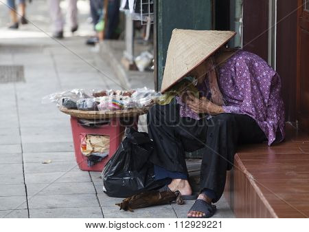 Asian vendor eating traditional cake as lunch meal on the sidewalk