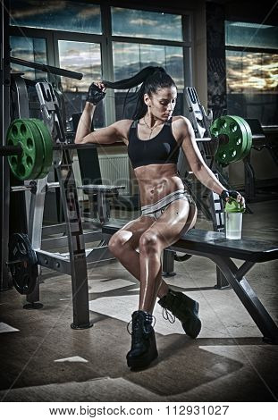 Gorgeous brunette lifting some weights and working on her biceps in a gym. Fitness woman