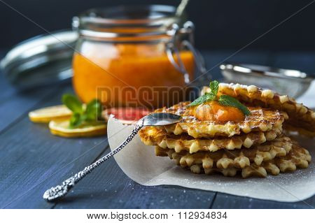 Wafers with drop of jam and silver spoon on paper