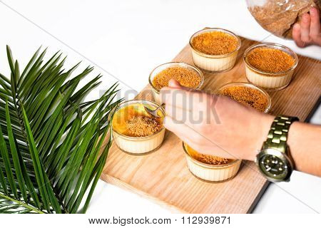 Woman's hands making creme brulee on wooden tray. Traditional French vanilla cream dessert with cara