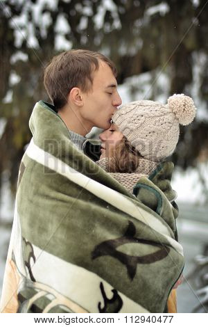Happy man kissing his beautiful girl on the forehead and covers her blanket (blanket).