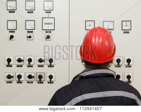 Technician Reading Instruments In Power Plant Control Center