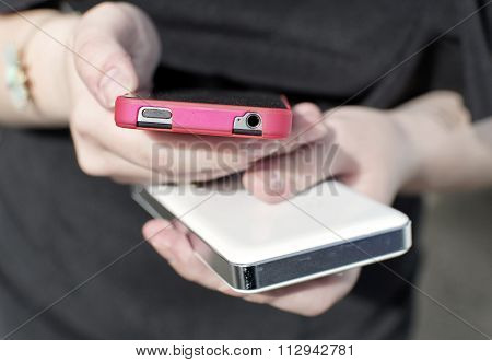 Two Cell Phone In The Girl's Hands
