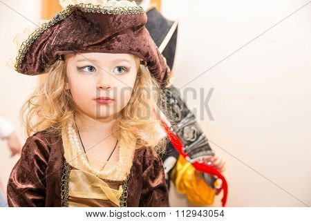 Little Girl Child Dressed As Pirate For Halloween  On Background Of Christmas Tree. Kid In Carnival