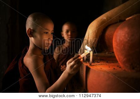 Portrait of young novice monks lighting up candlelight inside a Buddhist temple, low light setting, Bagan, Myanmar.