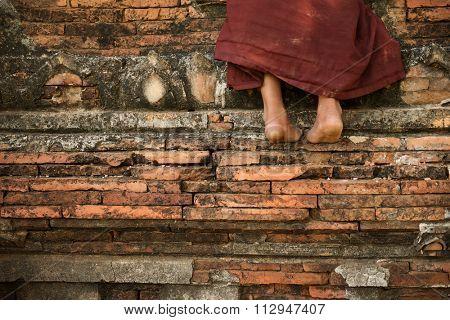 Young novice monk climbing up Buddhist temple, Bagan, Myanmar.