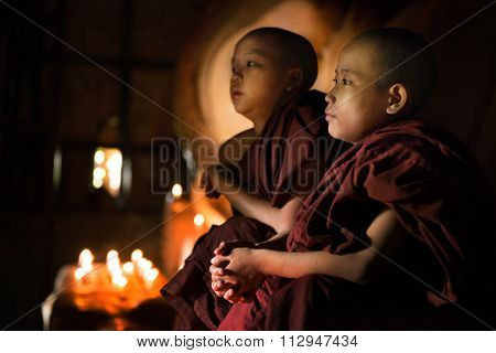 Young novice monks sitting inside a Buddhist temple, Bagan, Myanmar.